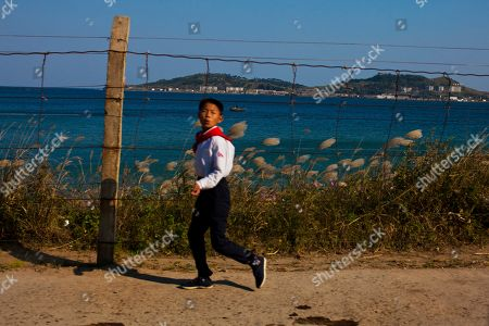 A North Korean boy walks along the coast, which is fortified by a security fence, near the town of Wonson, North Korea. It's hard to imagine a North Korea without Kim Jong Il, who led the nation for 17 years until his death on Dec. 17. His death marks the end of an era for North Korea, which has known only two leaders: Kim and his father, Kim Il Sung. Already, a new era has begun under the leadership of his young son, Kim Jong Un. Still, Kim Jong Il's presence is felt in every frame of a series of images made by Associated Press photographer David Guttenfelder. During the last months of Kim's life, Guttenfelder, along with AP Korea Bureau Chief Jean H. Lee, made several trips to North Korea