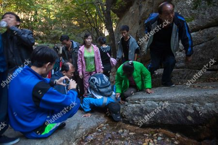 North Korean hikers drink from a natural spring during a hike on Mount Kumgang, North Korea. It's hard to imagine a North Korea without Kim Jong Il, who led the nation for 17 years until his death on Dec. 17. His death marks the end of an era for North Korea, which has known only two leaders: Kim and his father, Kim Il Sung. Already, a new era has begun under the leadership of his young son, Kim Jong Un. Still, Kim Jong Il's presence is felt in every frame of a series of images made by Associated Press photographer David Guttenfelder. During the last months of Kim's life, Guttenfelder, along with AP Korea Bureau Chief Jean H. Lee, made several trips to North Korea
