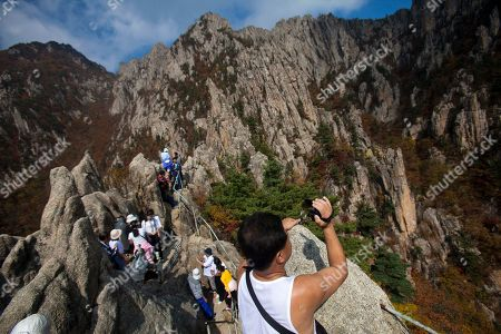 A North Korean man records video of the scenery as he and fellow hikers climb to a peak of Mount Kumgang, North Korea. It's hard to imagine a North Korea without Kim Jong Il, who led the nation for 17 years until his death on Dec. 17. His death marks the end of an era for North Korea, which has known only two leaders: Kim and his father, Kim Il Sung. Already, a new era has begun under the leadership of his young son, Kim Jong Un. Still, Kim Jong Il's presence is felt in every frame of a series of images made by Associated Press photographer David Guttenfelder. During the last months of Kim's life, Guttenfelder, along with AP Korea Bureau Chief Jean H. Lee, made several trips to North Korea