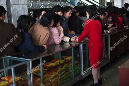 In this, a North Korean cashier helps customers at Pyongyang Department Store No. 1 in downtown Pyongyang, North Korea. It's hard to imagine a North Korea without Kim Jong Il, who led the nation for 17 years until his death on Dec. 17. His death marks the end of an era for North Korea, which has known only two leaders: Kim and his father, Kim Il Sung. Already, a new era has begun under the leadership of his young son, Kim Jong Un. Still, Kim Jong Il's presence is felt in every frame of a series of images made by Associated Press photographer David Guttenfelder. During the last months of Kim's life, Guttenfelder, along with AP Korea Bureau Chief Jean H. Lee, made several trips to North Korea