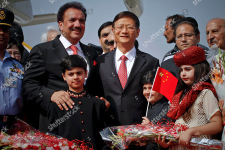 Chinese Public Security Minister Meng Jianzhu, center, and Pakistani Interior Minister Rehman Malik, second left, pose for photograph with children upon Jianzhu's arrival at Chaklala airbase in Rawalpindi, Pakistan on . China's top security official is visiting Pakistan for talks focusing on increased cooperation against Chinese militants who have found sanctuary in the northwest of the country