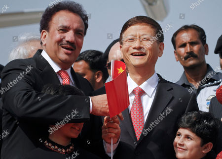 Chinese Public Security Minister Meng Jianzhu, second right, and Pakistani Interior Minister Rehman Malik, left, wave Chinese flag upon Jianzhu's arrival at Chaklala airbase in Rawalpindi, Pakistan on . China's top security official is visiting Pakistan for talks focusing on increased cooperation against Chinese militants who have found sanctuary in the northwest of the country