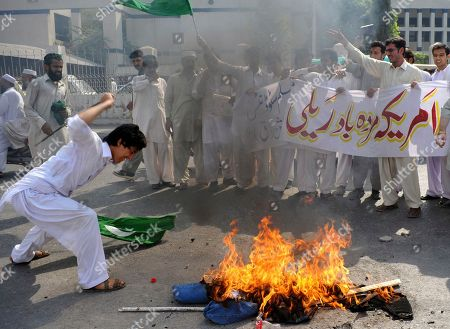"""A Pakistani protester beats a burning effigy of U. S. Adm. Mike Mullen, during an anti-American rally in Peshawar, Pakistan, on Tuesday, Oct, 4, 2011. U.S. pressure on Pakistan to attack Afghan militants on its soil will not succeed, the Pakistani prime minister told a gathering of political and military leaders. Banner reads """"Down with America rally"""