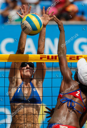 Emily Day, of the United States, left, spikes the ball as Puerto Rico's Yamileska Yantin tries to block during the women's beach volleyball bronze medal match at the Pan American Games in Puerto Vallarta, Mexico
