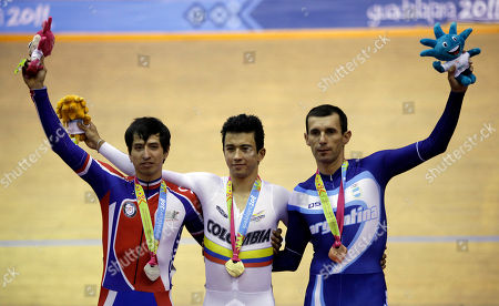 Silver medalist, Chile's Luis Mansilla, left, gold medalist, Colombia's Juan Arango, center, and bronze medalist, Argentina's Walter Perez, gesture from the podium after competing in the men's omnium 1km time trial cycling event at the Pan American Games in Guadalajara, Mexico