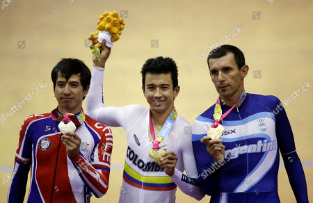 Silver medalist, Chile's Luis Mansilla, left, gold medalist, Colombia's Juan Arango, center, and bronze medalist, Argentina's Walter Perez, hold up their medals for the men's omnium 1km time trial cycling event at the Pan American Games in Guadalajara, Mexico