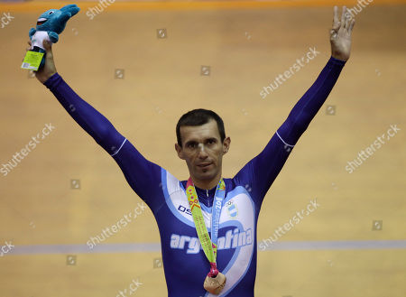 Bronze medal winner, Argentina's Walter Perez, gestures from the podium as he wears his medal for the men's omnium 1km time trial cycling event at the Pan American Games in Guadalajara, Mexico