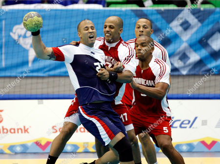 U.S. Clemons Axelsson, left, is challenged by Dominican Republic´s players Carlos Almeida, second from left, Manual Taveras, right, and Carlos Mirabal, back, during amen´s handball preliminary match at the Pan American Games in Guadalajara, Mexico