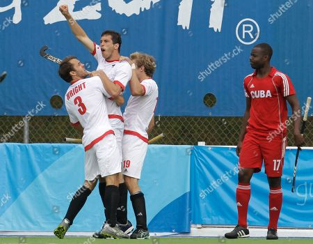 Canada's Matthew Guest, second from left, celebrates with teammate Philip Wright, left, and Iain Smythe after scoring as Cuba's Lazaro Garcia looks on during a men's semifinal hockey game at the Pan American Games in Guadalajara, Mexico