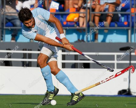 Stock Photo of Argentina's Lucas Cammareri hits the ball as the stick of Canada's Philip Wright flies past during the men's field hockey gold medal match at the Pan American Games in Guadalajara, Mexico, . Argentina won 3-1