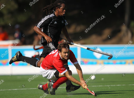 Canada's Andrew Wright, bottom, scores as Trinidad and Tobago's John Guest looks on during a men's hockey match at the Pan American Games in Guadalajara, Mexico