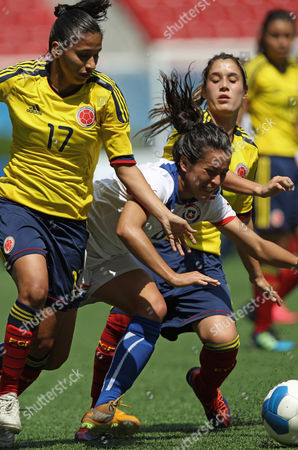 Chile's Maria Rojas, center, fights for the ball with Colombia's Carolina Arias and Daniela Montoya during a women's soccer match at the Pan American Games in Guadalajara, Mexico