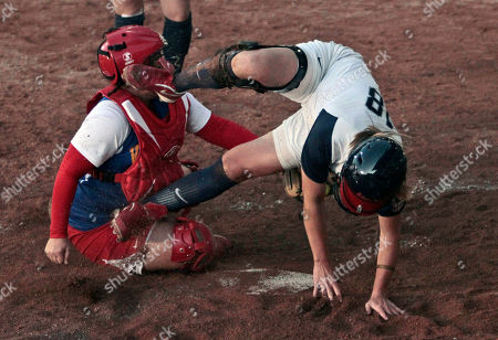Molly Johnson, from the United States, right, is tagged out at home plate by Venezuela's catcher Cristina Rodriguez during their women's preliminary softball game at the Pan American Games in Guadalajara, Mexico, . The United States won 10-0
