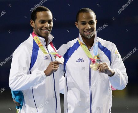 Cayman Island's Shaune Fraser, left, silver medal, and his brother Brett Fraser, gold medal, pose on the podium of the men's swimming 200m freestyle at the Pan American Games in Guadalajara, Mexico