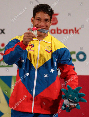 Stock Image of Silver medalist Venezuela's Junior Sanchez celebrates as he poses for pictures during the men's 69 kg weightlifting award ceremony at the Pan American Games in Guadalajara, Mexico