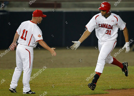 Stock Photo of Canada's Michael Crouse, right, is congratulated by third base coach Stubby Clapp after hitting a solo home run in the fourth inning to tie the Baseball World Cup first round game against Panama in Panama City