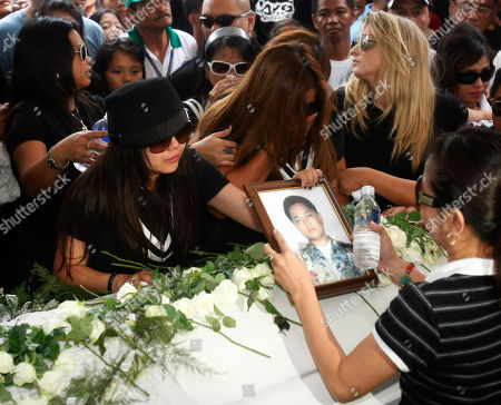 """Charice Pempengco, Raquel Pempengco Filipino singer Charice Pempengco of the TV hit """"Glee"""", left, holds a portrait of her estranged father Ricky Pempengco during interment at a memorial park at Cabuyao township, Laguna province south of Manila, Philippines. Ricky Pempengco was stabbed to death in nearby San Pedro township early this week by Angel Capili Jr. who later surrendered to police and admitted his crime"""