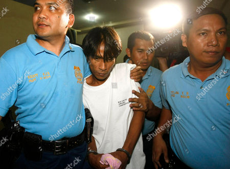 """Angel Capili Jr Police officers escort Angel Capili Jr., center, the suspect in the stabbing death of the estranged father of singer Charice Pempengco of the TV hit """"Glee"""" following his surrender at the Philippine National Police headquarters northeast of Manila, Philippines. Police said, Capili Jr., turned himself in to the chief of the home village in General Trias township township, Cavite province south of Manila"""