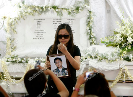 """Charice Pempengco Filipino singer Charice Pempengco of the TV hit """"Glee"""", poses with a portrait of her estranged father Ricky Pempengco's coffin at a funeral home at Muntinlupa city, south of Manila, Philippines. Ricky Pempengco was stabbed to death in nearby San Pedro township early this week by Angel Capili Jr. who later surrendered to police and admitted his crime"""