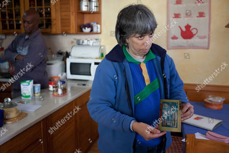 Maria do Rosario Valente shows a photo of a painting by her husband, captured American fugitive George Wright, background left, in the kitchen of their house, in Almocageme, outside Lisbon. Valente says in an interview with The Associated Press that her husband regrets his criminal past, including his 1962 New Jersey murder conviction, escape from a U.S. prison and hijacking of a plane in 1972. Wright, 68, was on the run for 41 years until his arrest in Portugal a month ago and is currently under house arrest