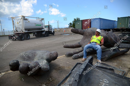 In this picture taken, Jose Rivera, a worker of the port of Mayaguez, rests on a giant hand, one of many pieces of a Christopher Columbus statue strewn across the port storage area in Mayaguez, Puerto Rico. The Columbus statue would be the tallest structure in the Caribbean and among the tallest statues in the world, a monument in a region where Columbus has not been regarded highly for many years