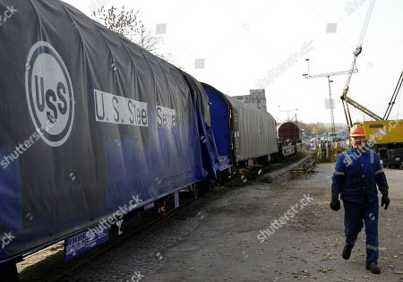 A worker passes by U.S. Steel rail wagon in the city of Smederevo, 45 kilometers east of Belgrade, Serbia. Serbia's government has agreed with U.S. Steel to buy back its loss-making plant in the Balkan country for a symbolic $1, with a goal to avoid its closure and the layoff of 5,400 of its workers, the Prime Minister Mirko Cvetkovic said Friday