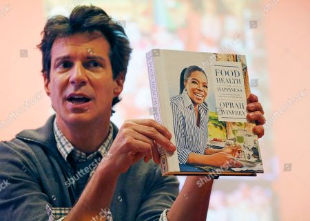 """Stock Photo of Adam Glassman O Magazine creative director Adam Glassman displays a copy of Oprah Winfrey's """"Food Health and Happiness,"""" during a sneak-preview of """"Oprah's Favorite Things,"""" containing the television personality's recipes for the weight conscious at the headquarters of """"O-The Oprah Magazine,"""", in New York"""