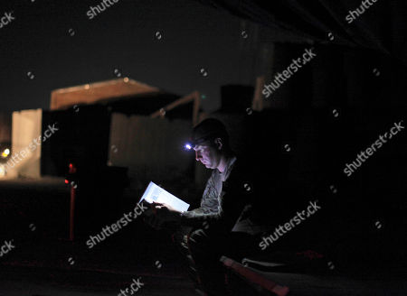 In this Chief Warrant Officer 2 Nick Stevenson from Clarksville Tn, from A company 7-101 Avation read a book at FOB Wilson in the outskirts of Kandahar, Afghanistan