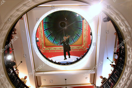 Stock Image of Violinist Shenzo Gregorio performs while strapped into a trapeze in the Queen Victoria Building in Sydney, . Gregorio plays to shoppers on three levels while he is suspended up to 25 meters (82 feet) in the air