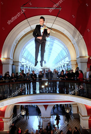 Violinist Shenzo Gregorio performs while strapped into a trapeze in the Queen Victoria Building in Sydney, . Gregorio plays to shoppers on three levels while he is suspended up to 25 meters (82 feet) in the air