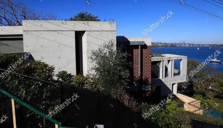 """The home of Madeleine Pulver, where bomb squad specialists safely freed Pulver after 10 hours with a device attached around her neck, in the Sydney suburb of Mosman overlooks Sydney Harbour, . Police are hunting for a masked man who chained a fake bomb to the young woman's neck after breaking into her wealthy family's home in an extortion attempt that Australia's Prime Minister Julia Gillard said resembled """"a Hollywood script"""