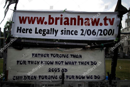 Stock Image of A sign dating how long Brian Haw has been protesting for, stands by a peace camp on the pavement surrounding Parliament Square opposite the Houses of Parliament in London, . It is 10 years today since Brian Haw began his peace campaign at the site which originally started as a protest over sanctions against Iraq. Haw is currently being treated for lung cancer in Germany