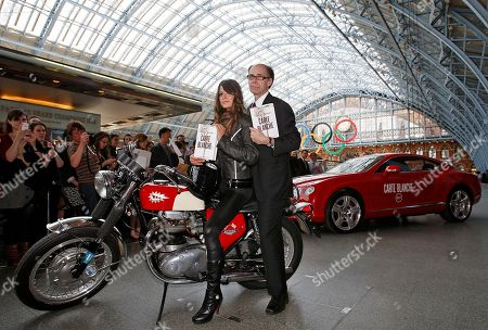 U.S. thriller writer Jeffery Deaver, right, poses for photographers with motorbike rider Chesca Miles as a Bond girl on a BSA spitfire next to a special Bentley Continental GT during a photo call for his new James Bond novel 'Carte Blanche' at St. Pancras International in London, . 'Carte Blanche' is due to be published by Hodder & Stoughton on the following day, Thursday, May 26