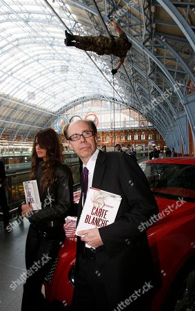 U.S. thriller writer Jeffery Deaver, right, poses for photographers with motorbike rider Chesca Miles as a Bond girl by a special Bentley Continental GT as a member of the Royal Marines Display Team hangs in the air in the background during a photo call for his new James Bond novel 'Carte Blanche' at St. Pancras International in London, . 'Carte Blanche' is due to be published by Hodder & Stoughton on the following day, Thursday, May 26