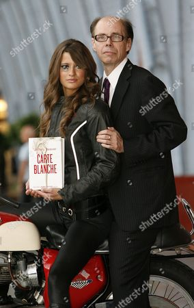 U.S. thriller writer Jeffery Deaver, right, poses for photographers with motorbike rider Chesca Miles as a Bond girl on a BSA spitfire during a photo call for his new James Bond novel 'Carte Blanche' at St. Pancras International in London, . 'Carte Blanche' is due to be published by Hodder & Stoughton on the following day, Thursday, May 26