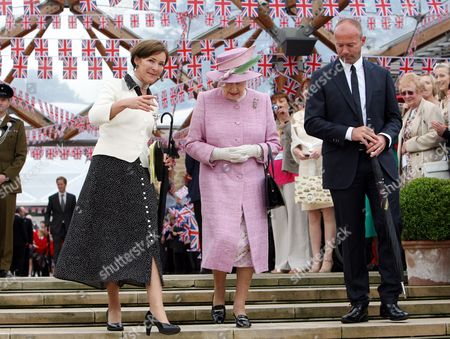 Britain's Queen Elizabeth II, center, Duchess of Northumberland, left, and Alan Shearer, right, at Alnwick Gardens in Alnwick, England, The Queen and Prince Philip are meeting with groups of volunteers and carers who have been invited to Alnwick to celebrate and recognise their work