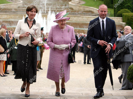 Britain's Queen Elizabeth II, center, Alan Shearer, right, and the Duchess of Northumberland, left, walk at Alnwick Gardens in Alnwick, England, The Queen and Prince Philip, unseen, are meeting with groups of volunteers and carers who have been invited to Alnwick to celebrate and recognise their work