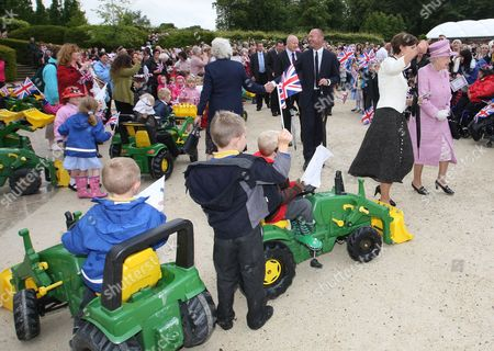 Britain's Queen Elizabeth II, right, and the Duchess of Northumberland, 2nd right, walk amongst the crowd at Alnwick Gardens in Alnwick, England, The Queen and her husband, Prince Philip, unseen, are meeting with groups of volunteers and carers who have been invited to Alnwick to celebrate and recognise their work