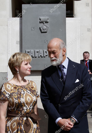Elena Gagarina, left, director of the Kremlin Museums in Moscow and daughter of Yuri Gagarin, the first man in space, and Britain's Prince Michael of Kent, right, pose for pictures after they unveiled a statue of Gagarin outside the headquarters of the British Council, in central London, . A gift from the Russian Space Agency (Roscosmos) to the British Council, the statue shows Gagarin standing on a globe in his space suit, and it will be installed at this location for a period of 12 months to mark the 50th anniversary of the first manned space flight