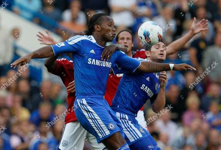 Chelsea's Didier Drogba, front left, and team mate Frank Lampard challenge for the ball with West Bromwich Albion's Somen Tchoyi (hidden), during their English Premiership soccer match at Chelsea's Stamford Bridge stadium in London, Saturday, Aug., 20, 2011