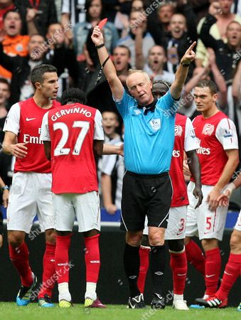 Arsenal's Gervinho, center, is shown a red card by referee Peter Walton, right, during their English Premier League soccer match against Newcastle United at St James' Park, Newcastle, England