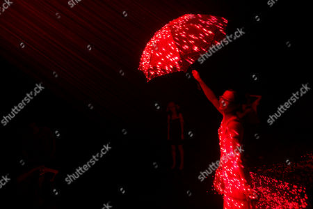 "A Chinese woman holds up an umbrella inside a laser light installation art titled ""V"" by Chinese artiste Li Hui displayed at a art gallery in Beijing, China"