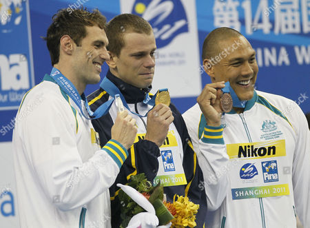 Cesar Cielo, Matthew Targett, Geoff Huegill Brazil's Cesar Cielo, center, shows his gold medal with Matthew Targett, silver, left, and Australia's Geoff Huegill, bronze, on the podium during an award ceremony for the men's 50m Butterfly event at the FINA Swimming World Championships in Shanghai, China