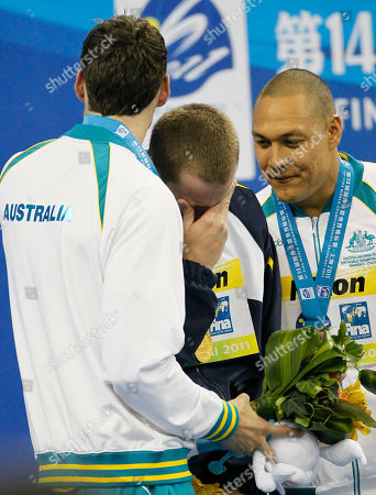 Cesar Cielo, Matthew Targett, Geoff Huegill Gold medalist Brazil's Cesar Cielo, center, reacts as he is comforted by Australia's Matthew Targett, silver, left, and Geoff Huegill, bronze, on the podium during an award ceremony for the men's 50m Butterfly event at the FINA Swimming World Championships in Shanghai, China