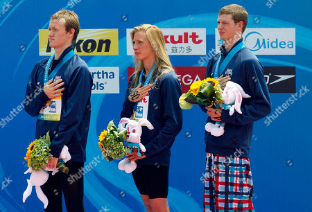 From left, gold medalists United States' Andrew Gemmel, Ashley Grace Twichell and Sean Ryan stands at attention as the U.S. national anthem is played during the medal ceremony for the 5km Team open water swimming event at the FINA Swimming World Championships at Jinshan Beach in Shanghai, China