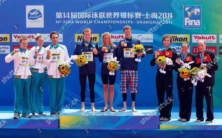 From left, silver medalists Australia's Rhys Mainstone, Melissa Gorman and Ky Hurst; gold medalists United State's Andrew Gemmel, Ashley Grace Twichell and Sean Ryan, bronze medalists Germany's Jan Wolfgarten, Isabelle Haerle and Thomas Lurz pose during the 5km Team open water swimming event medal ceremony at the FINA Swimming World Championships at Jinshan Beach in Shanghai, China