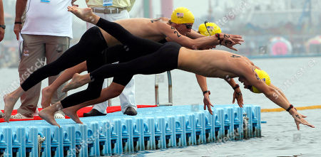 From left, gold medalists United States' Sean Ryan, Ashley Grace Twichell and Andrew Gemmel start the 5km Team open water swimming event at the FINA Swimming World Championships at Jinshan Beach in Shanghai, China