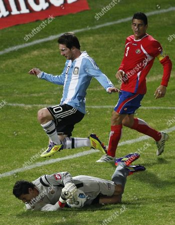 Argentina's Lionel Messi, top left, jumps over Costa Rica's goalkeeper Leonel Moreira as Costa Rica's Johnny Acosta watches during a group A Copa America soccer match in Cordoba, Argentina