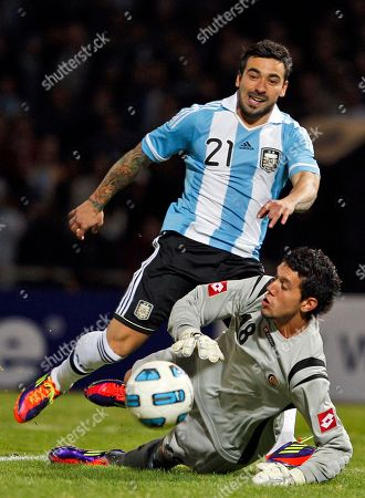 Argentina's Ezequiel Lavezzi, top, misses a chance to score as Costa Rica's goalkeeper Leonel Moreira fails to block during a group A Copa America soccer match in Cordoba, Argentina, . Argentina won 3-0