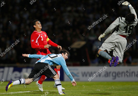 Costa Rica's goalkeeper Leonel Moreira, top, saves a shot by Argentina's Lionel Messi, left, as Costa Rica's Johnny Acosta looks on during a group A Copa America soccer match in Cordoba, Argentina